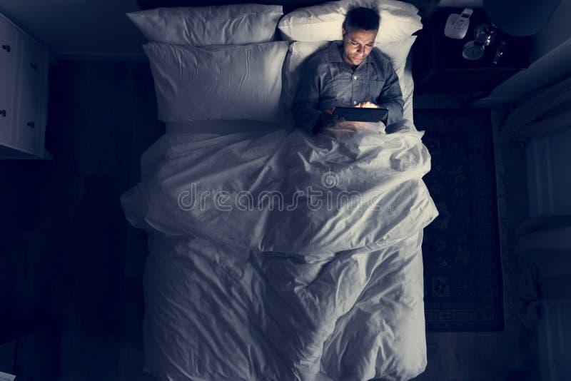 Hombre en cama usando su tableta imagen de archivo libre de regalías