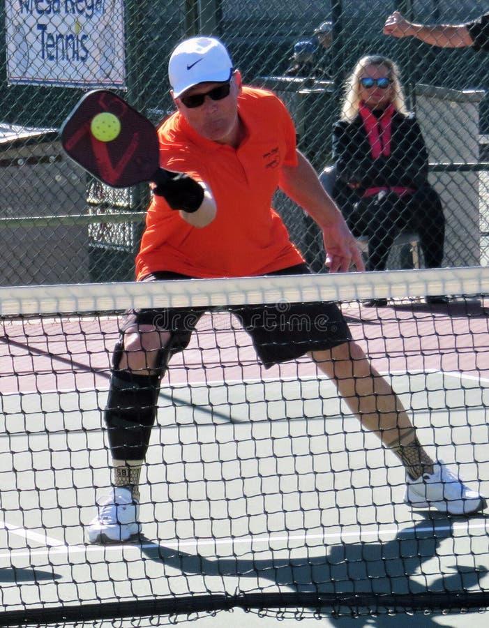 Hombre en camisa anaranjada y el casquillo blanco que muestran habilidades en el torneo de Pickleball fotos de archivo
