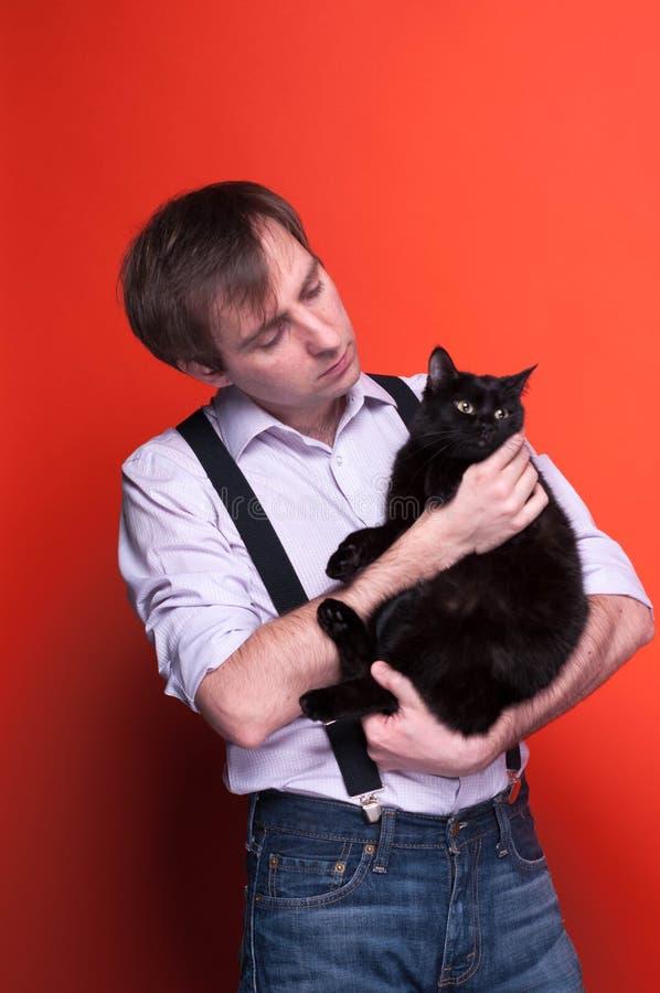 Hombre en camisa con rodado encima de las mangas y de la liga que sostienen el gato negro, mirándola imagen de archivo libre de regalías