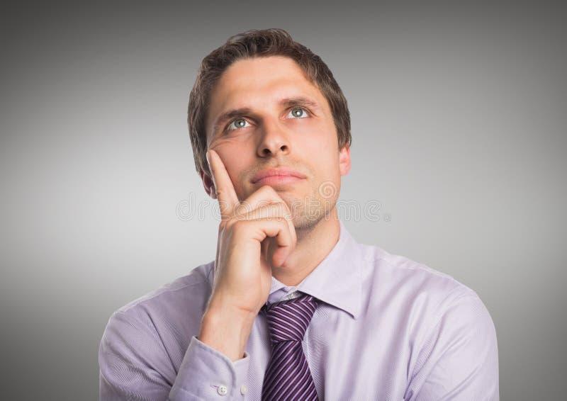 Hombre en camisa de la lavanda que piensa contra fondo gris fotografía de archivo libre de regalías