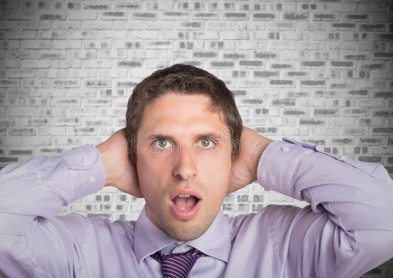 Hombre en camisa lavendar con las manos en la cabeza contra la pared de ladrillo blanca imagen de archivo