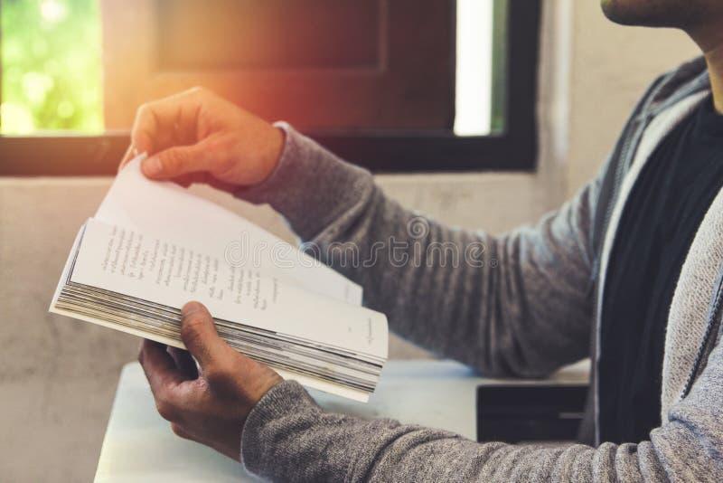 Hombre en camisa negra y prueba gris del libro de lectura de la sentada de la sudadera con capucha en la tabla foto de archivo