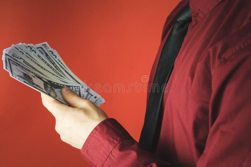 hombre en camisa roja con una tenencia un paquete de cuentas en su mano en un fondo rojo fotos de archivo libres de regalías