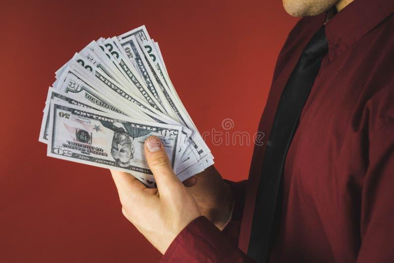 hombre en camisa roja con una tenencia un paquete de cuentas en su mano en un fondo rojo fotos de archivo