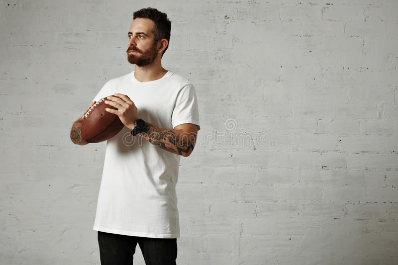 Hombre en camiseta blanca en blanco con un fútbol del vintage fotografía de archivo libre de regalías