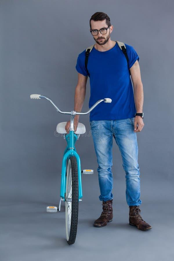 Hombre en camiseta y mochila azules con una bicicleta imagen de archivo