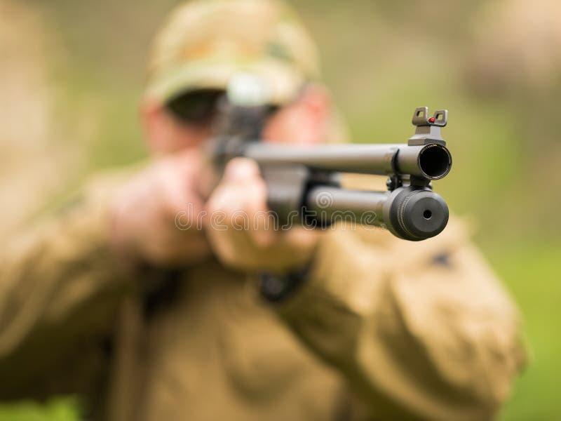Hombre en camuflaje con una escopeta que tiene como objetivo una blanco fotos de archivo libres de regalías