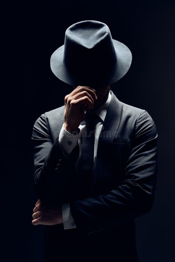 Hombre en cara de ocultaci?n del traje detr?s de su sombrero aislado en fondo oscuro fotografía de archivo