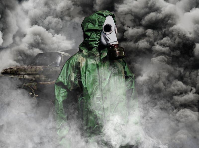Hombre en careta antigás y capa de la protección química en el humo de vehículos fotografía de archivo libre de regalías