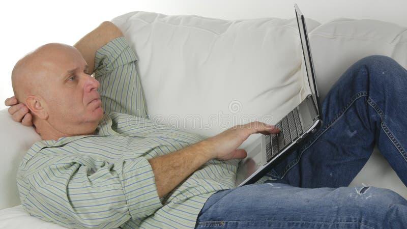 Hombre en casa que sienta y que descansa sobre Sofa Doing Business Using un ordenador portátil fotografía de archivo