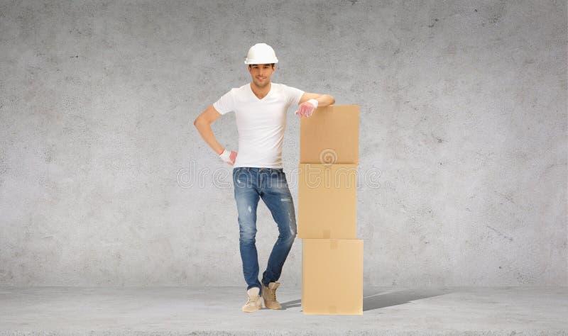 Hombre en casco con la torre de las cajas de cartón imagen de archivo libre de regalías
