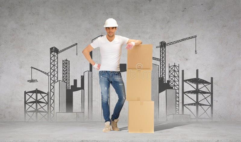 Hombre en casco con la torre de las cajas de cartón fotografía de archivo libre de regalías