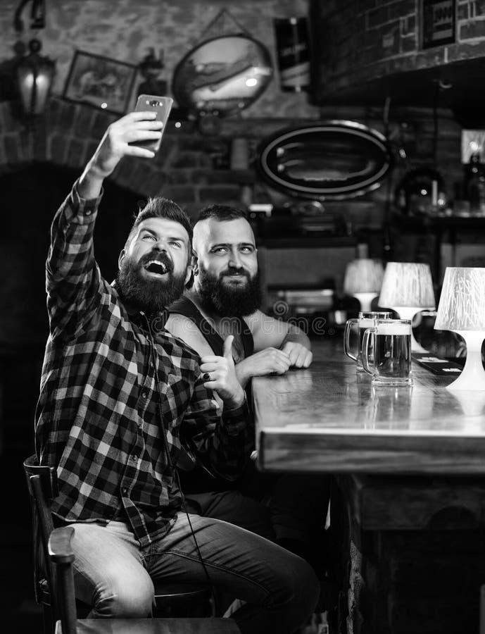 Hombre en cerveza de consumici?n de la barra Foto del selfie de la toma para recordar la gran tarde en pub Comunicaci?n en l?nea  fotografía de archivo libre de regalías