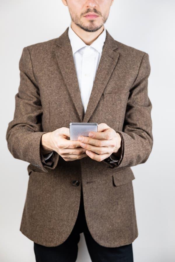 Hombre en chaqueta de tweed con un teléfono móvil imagen de archivo libre de regalías