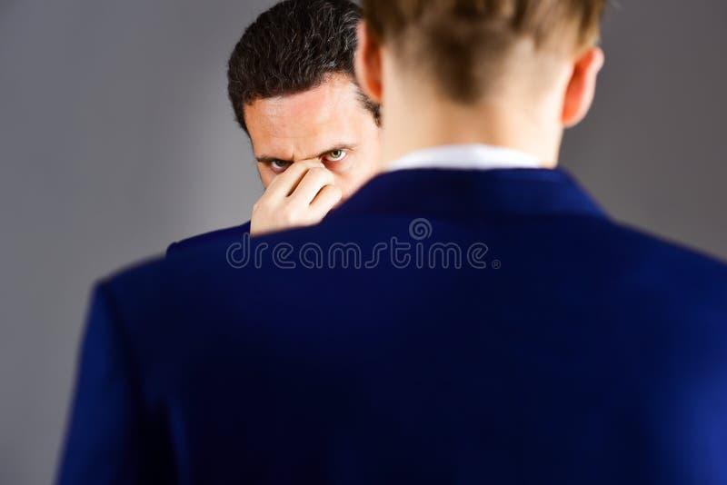 Hombre en chaqueta que escucha su socio con la expresión subrayada foto de archivo libre de regalías