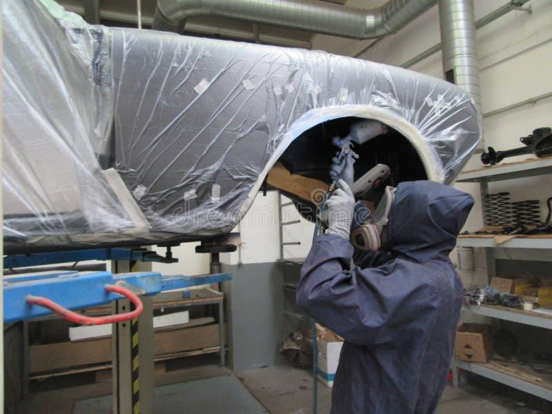 Hombre en coche de la pintura de la bata en garaje de la pintura fotos de archivo