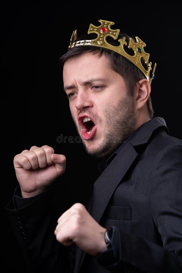 Hombre en corona y traje de negocios imagen de archivo