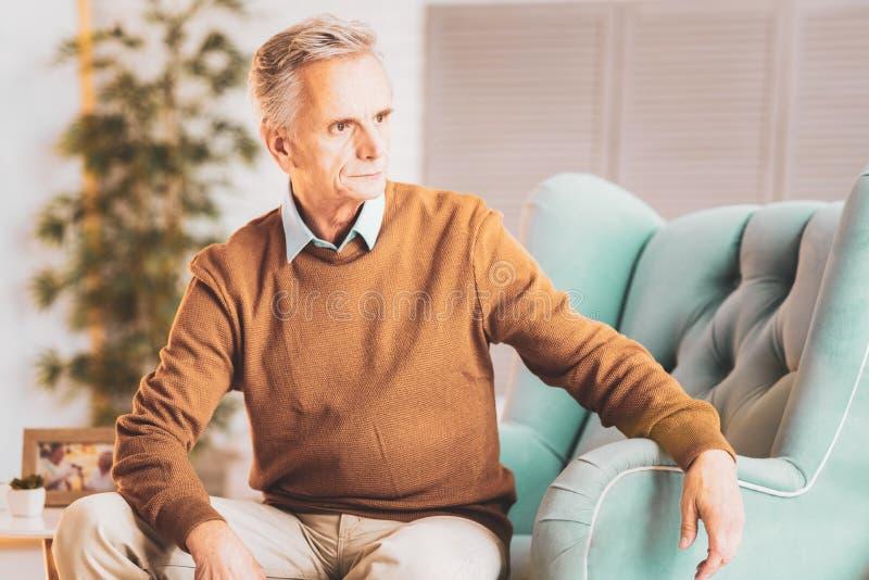 Hombre en cuestión envejecido que se sienta en sala de estar moderna ligera foto de archivo libre de regalías