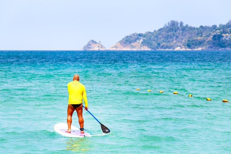Hombre en del levantar el tablero de paleta en el mar Riegue la diversi?n fotos de archivo