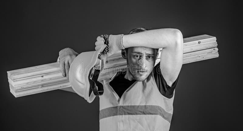 Hombre en el barrido del casco y de los guantes protectores sudado de la frente, fondo azul Concepto cansado del trabajador carpi fotografía de archivo libre de regalías