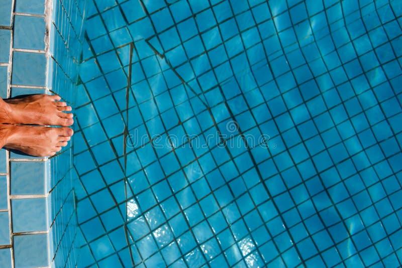 Hombre en el borde de la piscina fotos de archivo