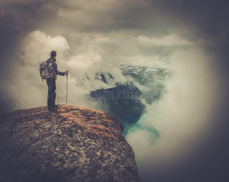Hombre en el borde de la roca imagenes de archivo