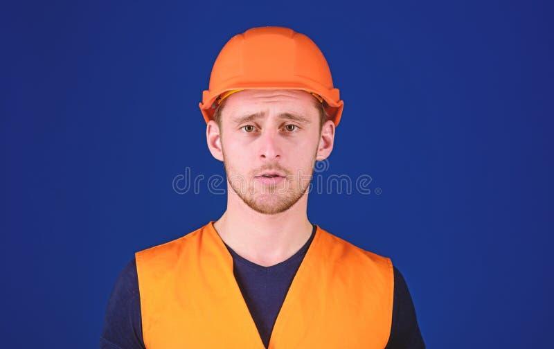 Hombre en el casco protector, el casco y el uniforme de trabajo, fondo azul Trabajador, contratista, constructor en cara tranquil fotografía de archivo