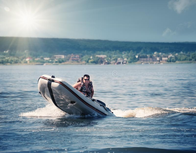 Hombre en el chaleco salvavidas que conduce el barco de motor de goma fotografía de archivo