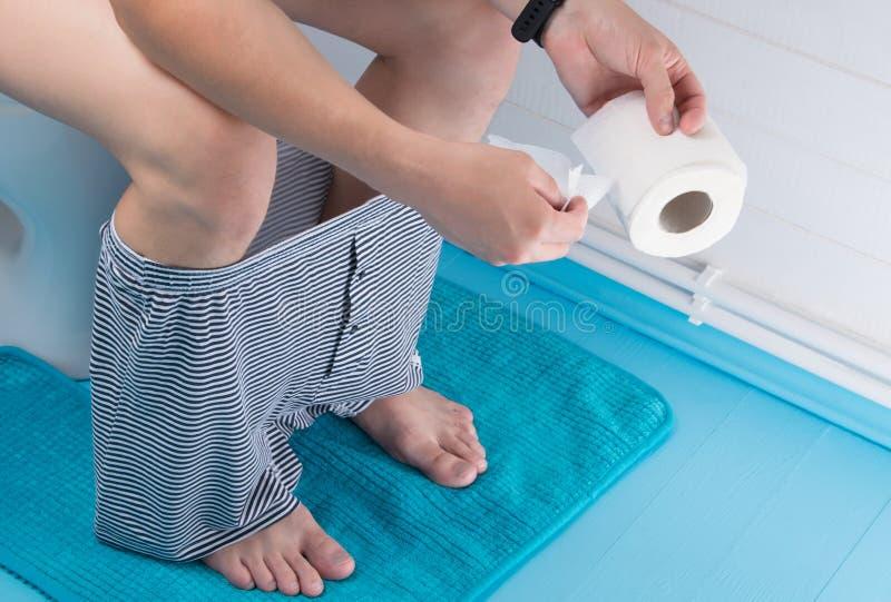 Hombre en el cuarto de baño, zafando un pedazo de papel higiénico imagenes de archivo