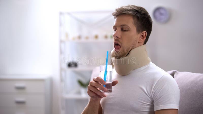 Hombre en el cuello cervical de la espuma que intenta beber el agua de cristal con la paja, tentativa pobre imagen de archivo