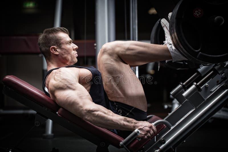 Hombre en el entrenamiento del gimnasio en la prensa de la pierna fotos de archivo