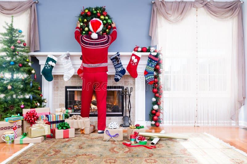 Hombre en el equipo de Papá Noel que adorna para la Navidad fotos de archivo