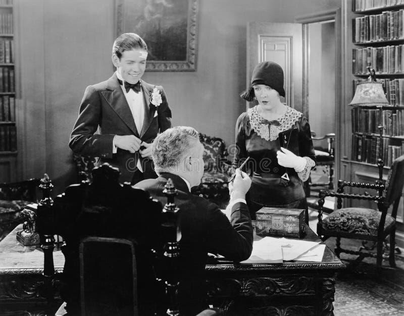 Hombre en el escritorio que habla a la mujer y hombre joven (todas las personas representadas no son vivas más largo y ningún est fotografía de archivo libre de regalías