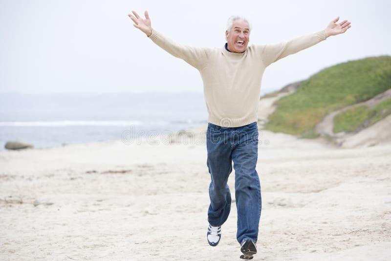 Hombre en el funcionamiento y la sonrisa de la playa fotografía de archivo