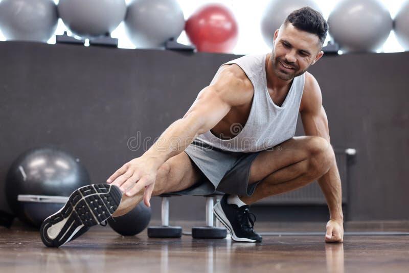 Hombre en el gimnasio que hace estirando ejercicios en el piso imágenes de archivo libres de regalías