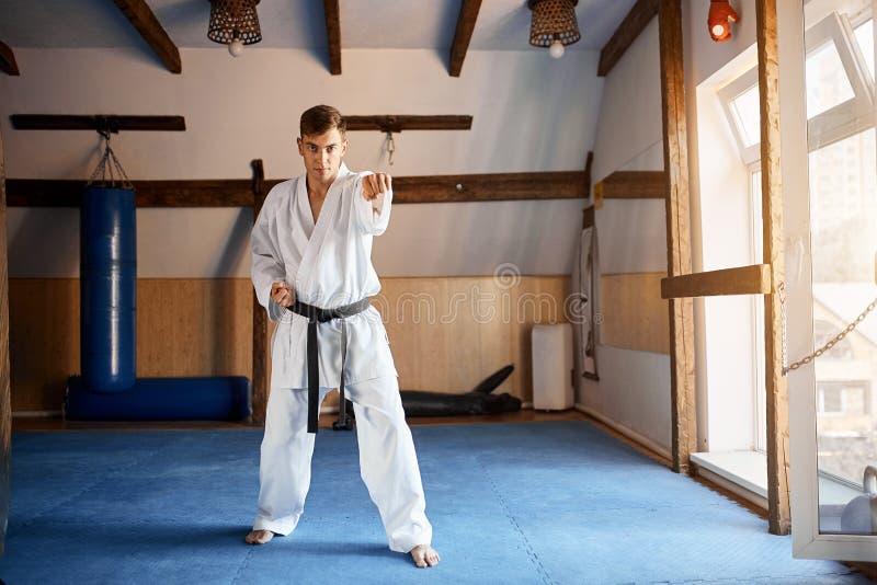 Hombre en el kimono blanco con karate del entrenamiento de la correa negra en gimnasio fotos de archivo