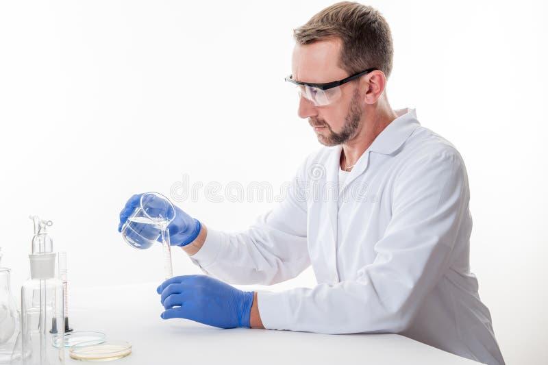 Hombre en el laboratorio, opinión un hombre en el laboratorio mientras que experimenta la ejecución foto de archivo libre de regalías