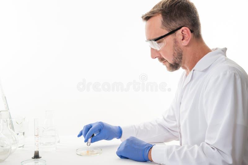 Hombre en el laboratorio, opinión un hombre en el laboratorio mientras que experimenta la ejecución fotos de archivo libres de regalías