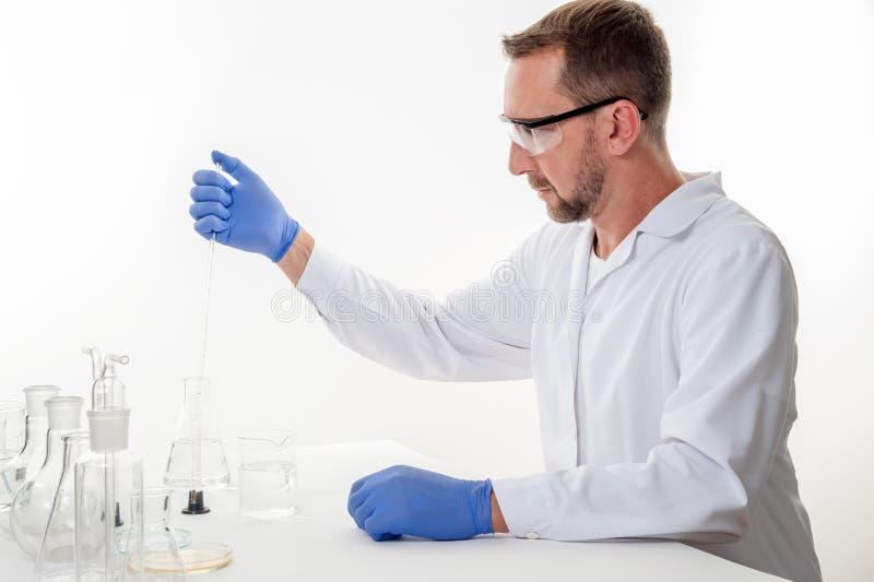 Hombre en el laboratorio, opinión un hombre en el laboratorio mientras que experimenta la ejecución imagenes de archivo