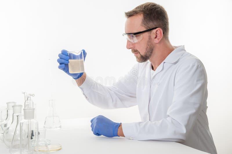Hombre en el laboratorio, opinión un hombre en el laboratorio mientras que experimenta la ejecución imagen de archivo