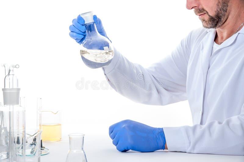 Hombre en el laboratorio, opinión un hombre en el laboratorio mientras que experimenta la ejecución fotografía de archivo