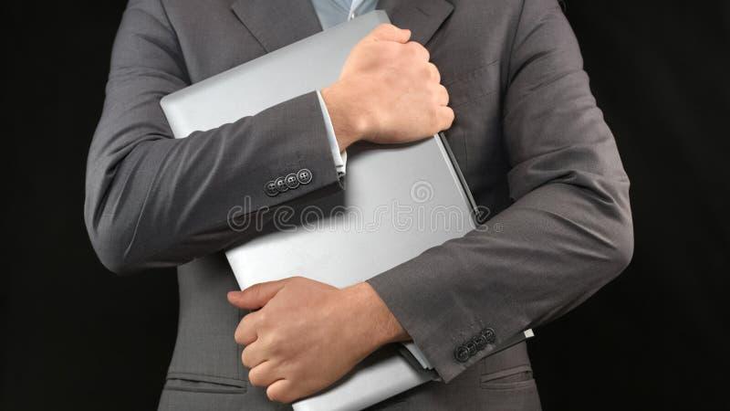 Hombre en el ordenador portátil de la tenencia del traje, seguridad informática, protección de datos personal, aislamiento imagen de archivo libre de regalías