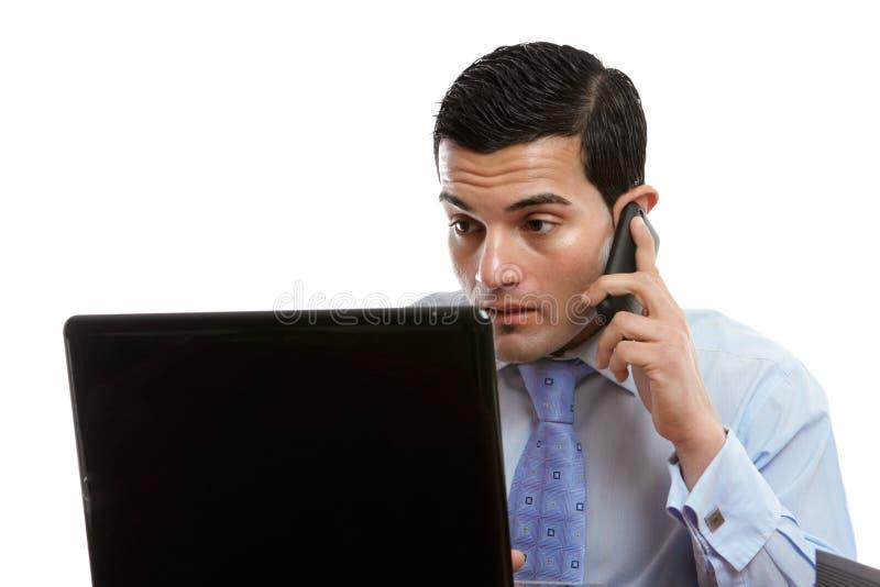 Hombre en el ordenador que hace o que recibe llamada de teléfono foto de archivo libre de regalías