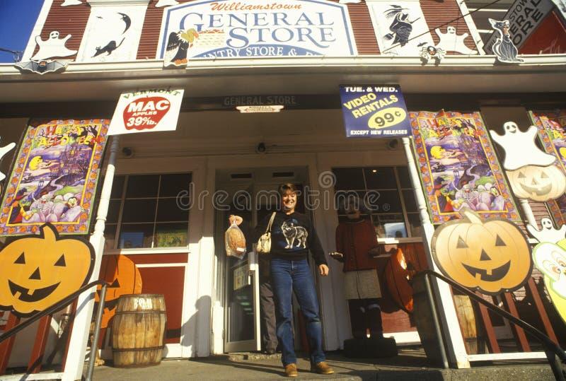 Hombre en el pórtico de la tienda rural en Williamstown, VT cubierto con las decoraciones de Halloween fotos de archivo