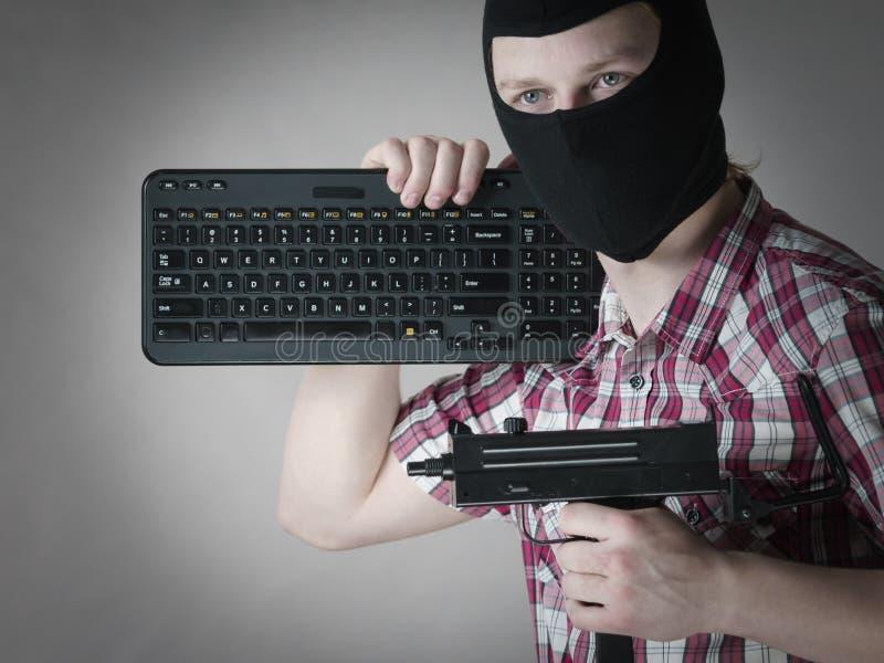Hombre en el pasamontañas que sostiene el teclado y el arma fotografía de archivo libre de regalías