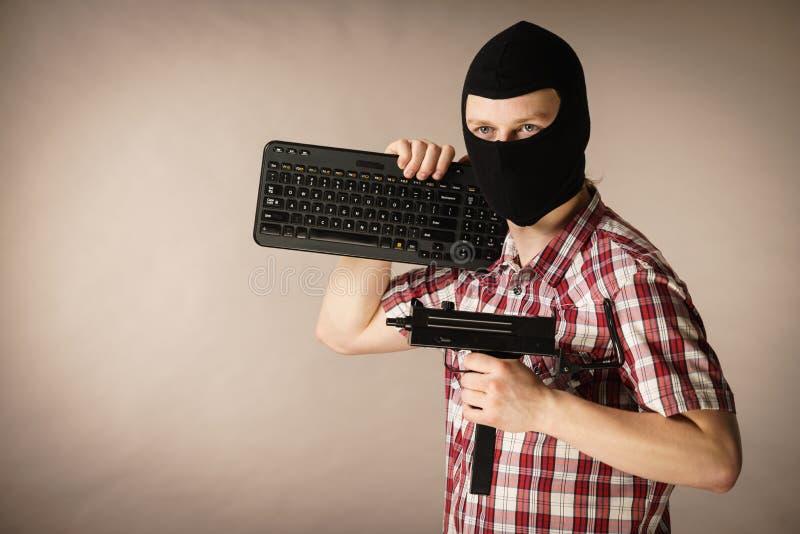 Hombre en el pasamontañas que sostiene el teclado y el arma foto de archivo