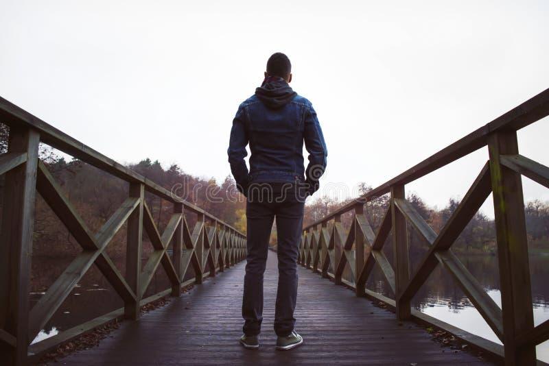 Hombre en el puente de madera sobre un lago, en un día húmedo del otoño imagen de archivo libre de regalías