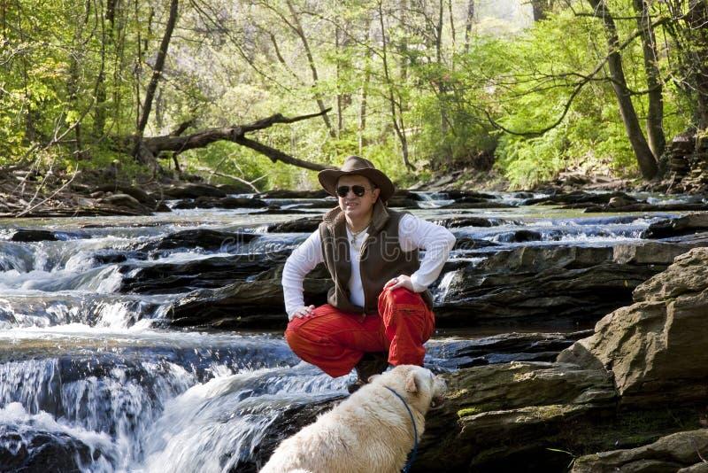 Hombre en el río con el perro que mira a la distancia foto de archivo