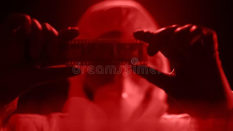 Hombre en el rollo de observación de la cámara del traje del laboratorio, fotografía que se convierte en luz roja foto de archivo libre de regalías