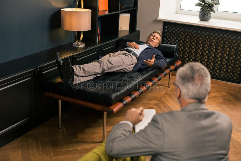 Hombre en el sofá que habla con un psicoterapeuta foto de archivo libre de regalías